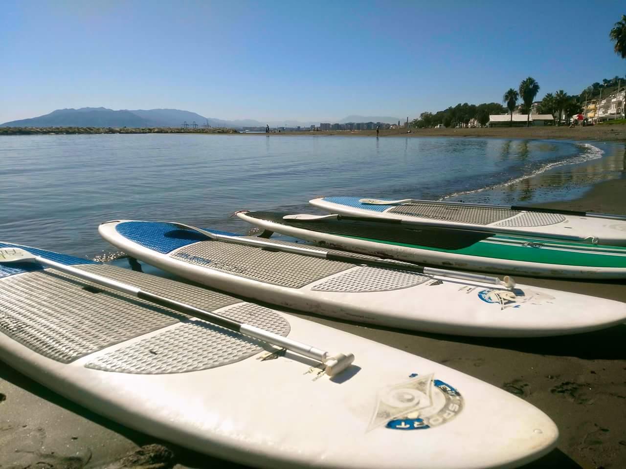Cuatro tablas de Paddle Surf tomando sol en la orilla de la playa de El Palo
