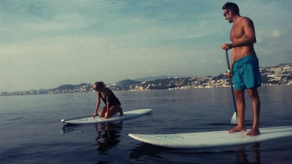 Dos personas en el mar encima de tablas de Paddle Surf en frente de El Palo haciendo una clase.