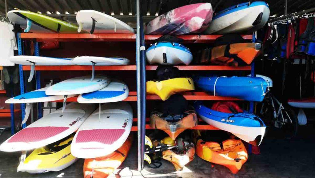 Estanteria en Kayak Y Bike lleno de tablas de Paddle Surf y Kayaks