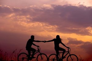Dos personas disfrutando un paseo romántico en bicicleta durante el atardecer