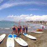 Un grupo de siete personas disfrutando una clase de Paddle Surf en las playas de El Palo.