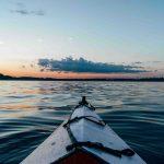 Kayak blanco mirando el horizonte en aguas tranquillas