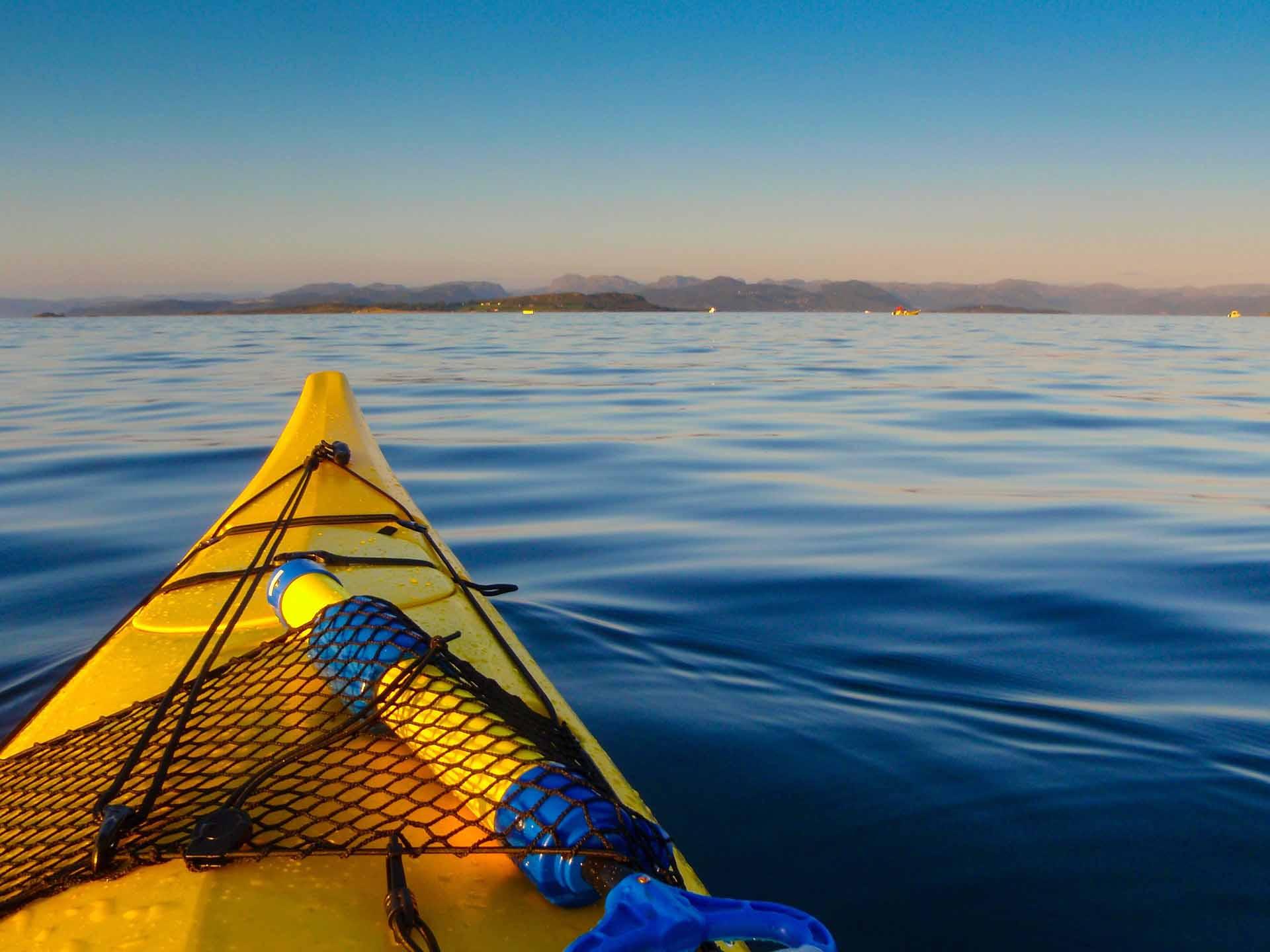 Kayak amarillo tranquilamente flotando en el mar