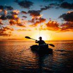 Un hombre en un Kayak de pesca paleando para el horizonte durante el atardecer
