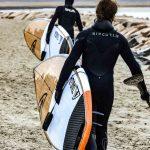 Dos chicos caminando por la playa con Tablas de Paddle Surf para olas
